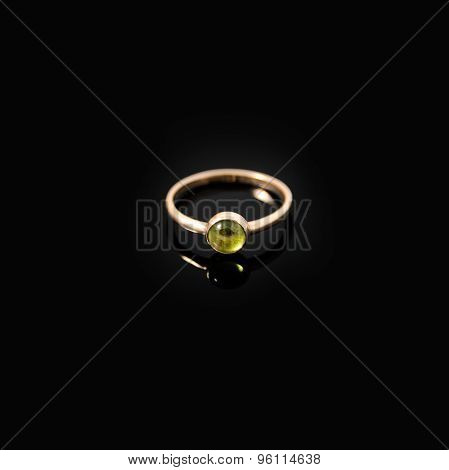 Luxury jewellery. Yellow gold ring with green gemstone on black background. Selective focus.