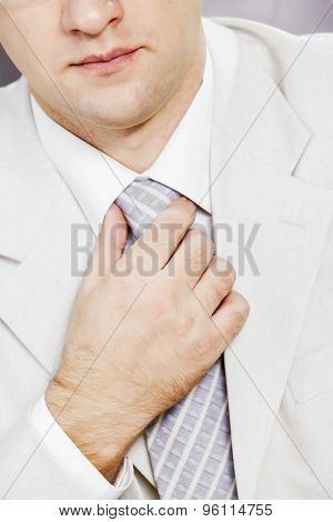 Close up of businessman in a business suit correcting his tie
