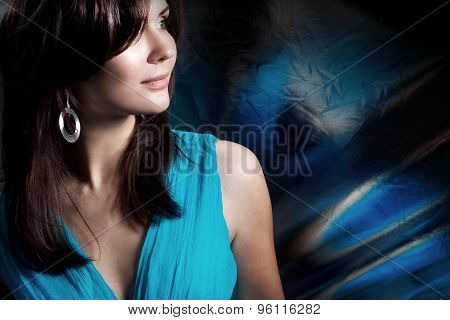 beautiful long-haired woman in a blue dress on dark background