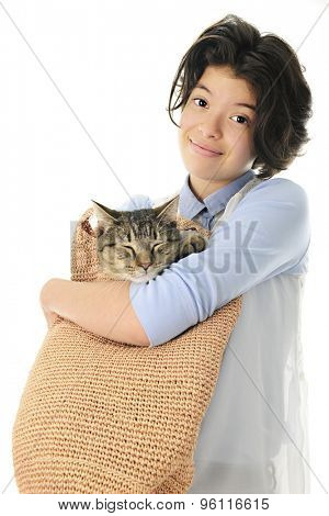 An attractive young teen holding her sleeping cat in a tan woven shoulder-strap bag. Focus on the girl.  On a white back ground.