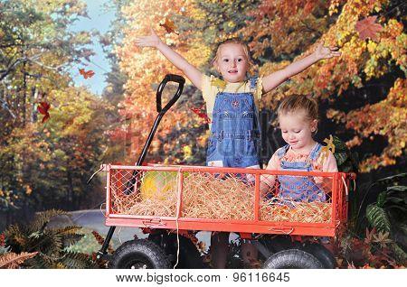 Two preschool sisters enjoying a colorful fall day in a work wagon.