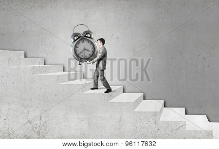 Young businessman carrying with effort huge alarm clock