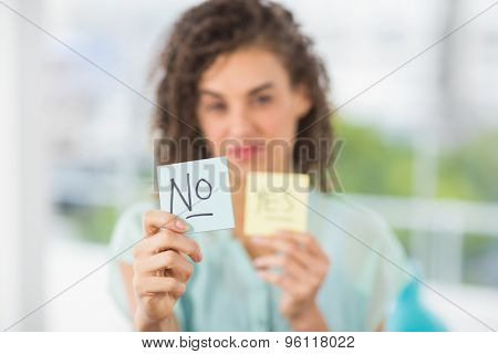 Portrait of a smiling businesswoman holding yes and no sticks