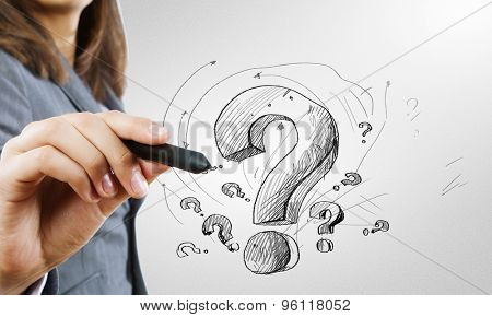 Close up of business woman drawing question mark