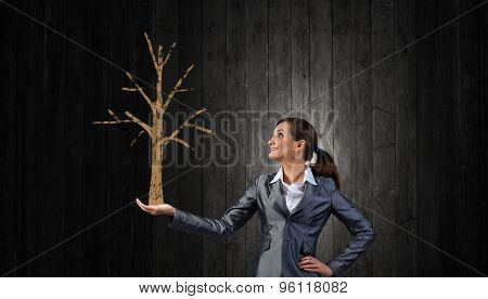 Young businesswoman showing money tree in her hand