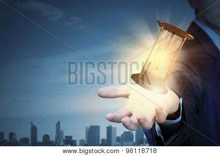 Close up of businessman with sandglass presenting time concept