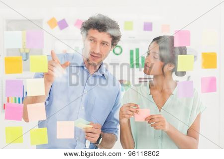 Puzzled business team looking at notes on the wall in the office