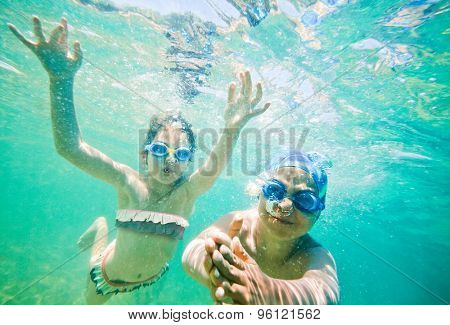 Two kids - boy and a girl, about seven years old are swimming underwater in a sea or ocean.