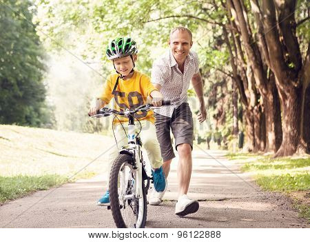 Father teaches his son how to ride the bicykle