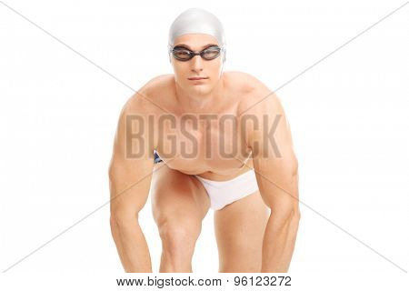 Studio shot of a young male swimmer in white swim trunks getting ready to jump isolated on white background