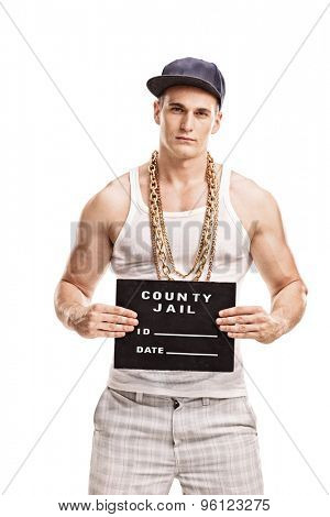 Vertical shot of a young male gangster posing for a mug shot isolated on white background