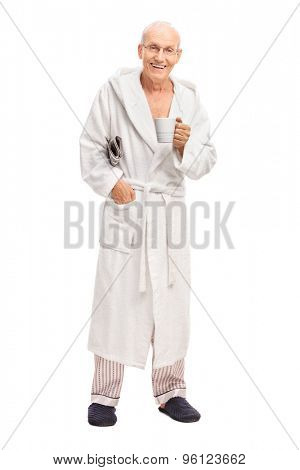 Full length portrait of a senior man in a white bathrobe holding a newspaper and a coffee mug isolated on white background