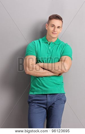 Vertical shot of a casual young man leaning against a gray wall and looking at the camera