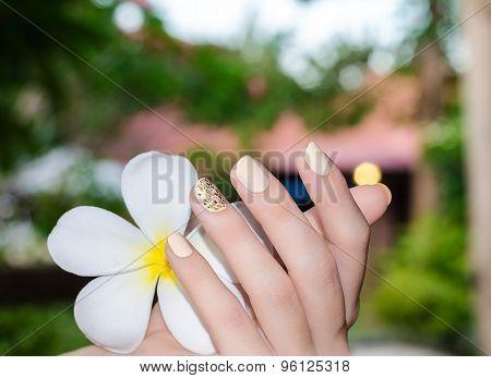 White plumeria in female hand with bright yellow nail design