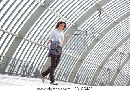 Business Woman Walking And Looking At Mobile Phone