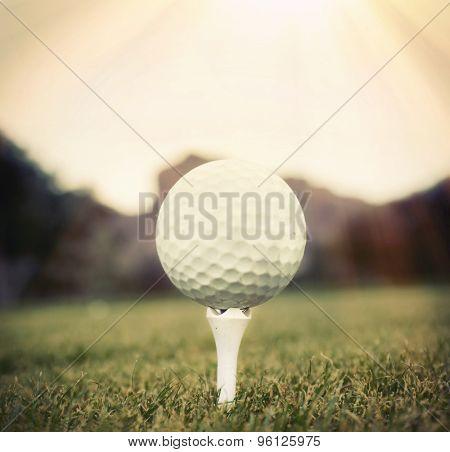 Golf ball on tee with sun shining down