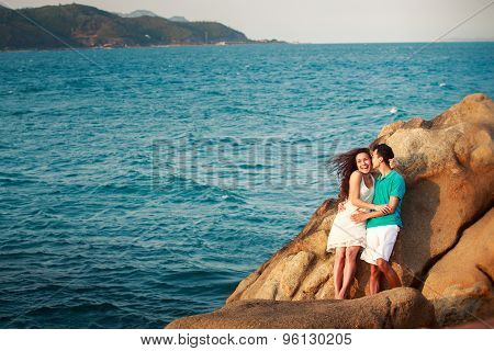 Girl And Guy On Stone Against Sea