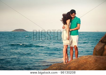 Girl And Guy Hug On Stone Against Azure Sea