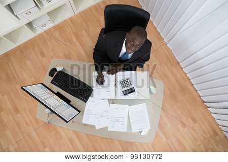 Businessman Calculating Bills In Office