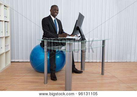 Businessman Working Sitting On Pilates Ball