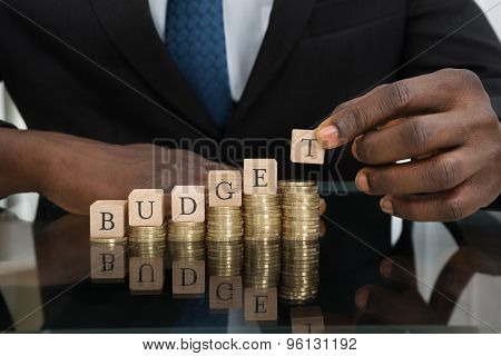 Businessman Putting The Letters Of The Word Budget On Coins