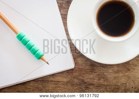 Pencil On Open Blank Notebook With Coffee Cup