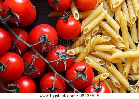 Small Red Tomatoes On The Vine, Dry Penne Pasta, On Black Wood From Above.