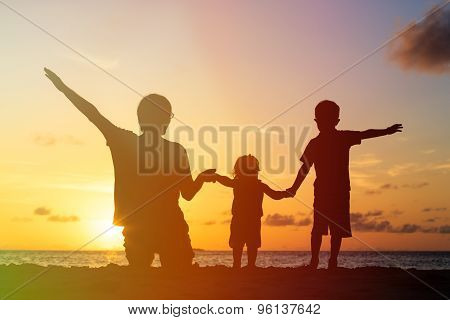 father with two kids at sunset beach