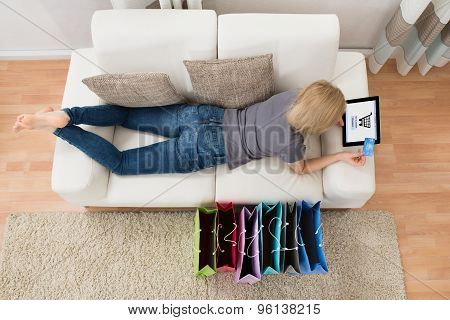 Woman Lying On Sofa With Digital Tablet And Shopping Bags