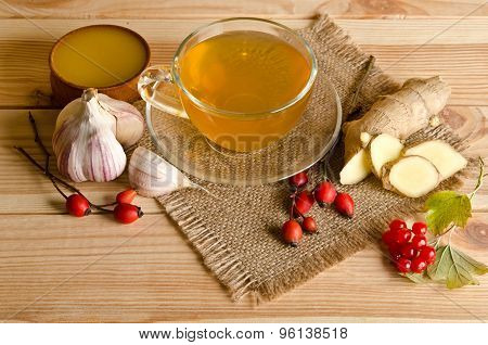 Cup Of Tea,slices Of Ginger,honey,rosehip Berries And Viburnum On A Wooden Table
