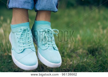 Female Legs In Jeans And Sport Shoe Floating In The Air Above The Green Grass In The Park