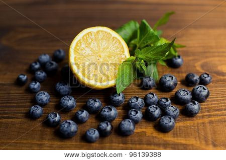 Fresh great bilberries with lime  on wooden ground
