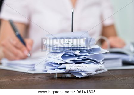Bills In Paper Nail With Businessperson At Desk