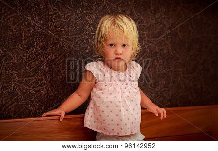 Portrait Of Standing Little Blonde Girl In Pink Against Brown Wall