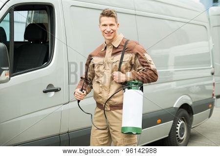 Young Worker With Pesticide In Front Van