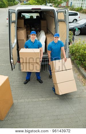 Two Workers Loading Cardboard Boxes In Truck