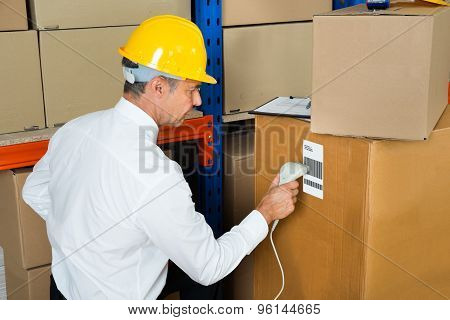 Manager Scanning Cardboard Box With Barcode Scanner