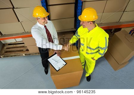Happy Warehouse Manager And Worker Shaking Hands