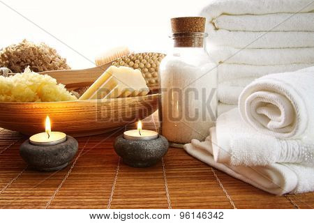 Spa setting with candles, sea salt and towels