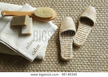 Straw slippers with spa accessories on carpet