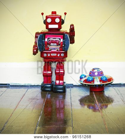 retro robot toy and ufo on old wooden floor