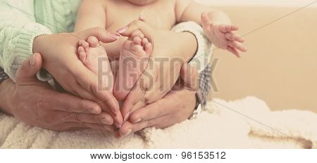 Newborn baby on father and mother hands, close-up