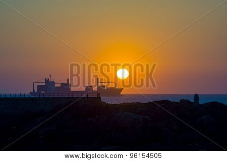 Cargo ship at sunset in the Atlantic Ocean