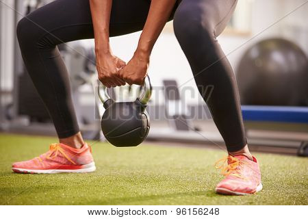Woman exercising with a kettlebell weight, low-section crop
