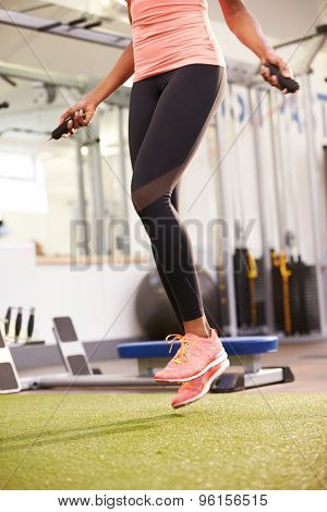 Healthy young woman skipping rope in a gym, crop