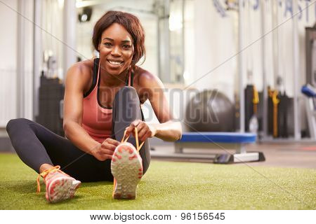Young woman sitting in a gym tying her shoelaces