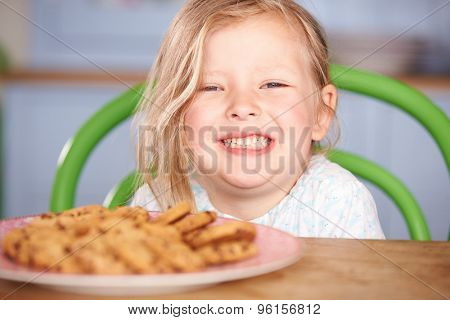 Young Girl Sitting At Table With Plate Of Cookies