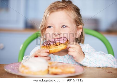 Young Girl Sitting At Table Eating Iced Donut