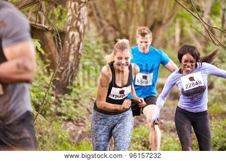 Three competitors running in a forest at an endurance event