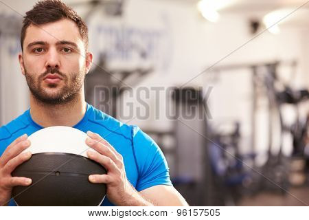 Portrait of a man holding medicine ball at a gym, copy space